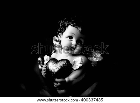 Cherub angel statue with heart,Double exposure cherub angel with rose,Love concept,Black and white - stock photo