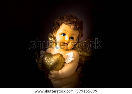Cherub angel statue with heart,Love concept - stock photo