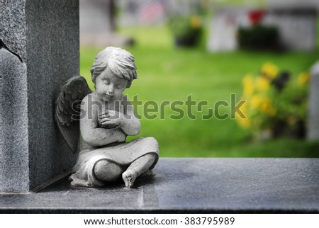 Cherub angel statue with wings carved from granite stone religious symbol brining hope and love - stock photo