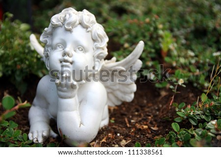 cherub in a natural background in a german's cemetery - stock photo