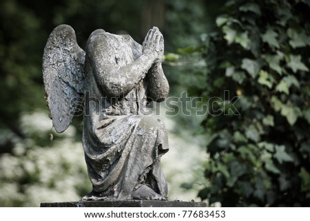 Cherub without head. Damaged statue on old cemetery. - stock photo