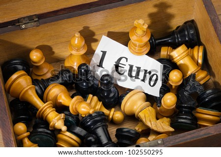 Chess and Euro - close-up of chessmen as a detail at the flea market for sale as euro crisis symbol image. - stock photo