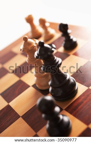 chess back and white queens face each other selective focus - stock photo