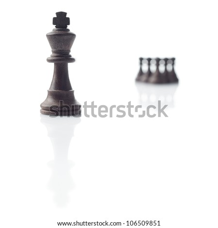 Chess. Black king, five pawns out of focus and their shadows on white background - stock photo