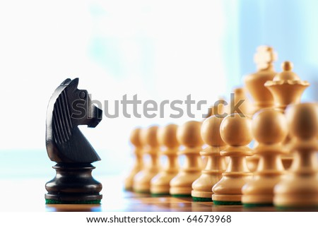 Chess black knight challenges white pawns abstract background - stock photo