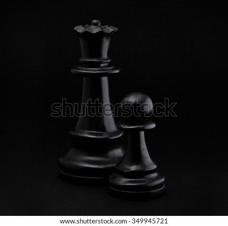 Chess. Black Pawn and Queen on black background. - stock photo