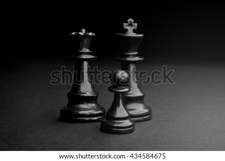 Chess. Black Pawn, King and Queen on black background. - stock photo