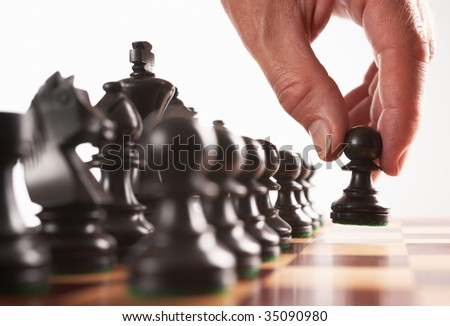 chess black player first move hand moves pawn selective focus - stock photo