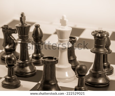 Chess board game in checkmate with white king among black chess