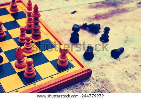 Chess board with chess pieces on a vintage wooden background - stock photo