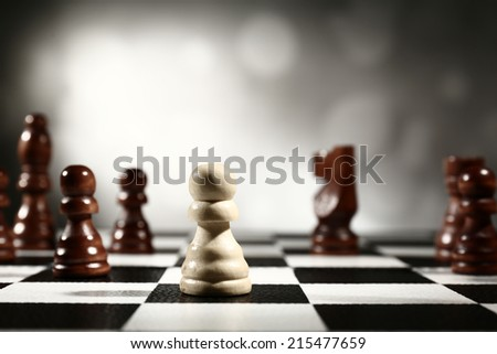 Chess board with chess pieces on grey background - stock photo