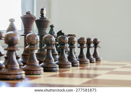 Chess board with chess pieces on light background - stock photo