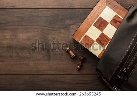 chess board with figures in the brown bag on wooden table - stock photo