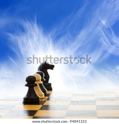 Chess board with figures on blue sky background - stock photo