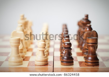 chess board with figures on grey background - stock photo