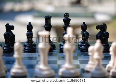 Chess board with focus on the black chessmen - stock photo