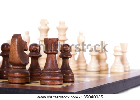 Chess board with starting positions aligned chess pieces, isolated on white background. - stock photo