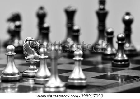 Chess board with white knight facing opponent in match - stock photo