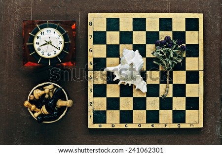 Chess, clock and seashell on old wooden background - stock photo