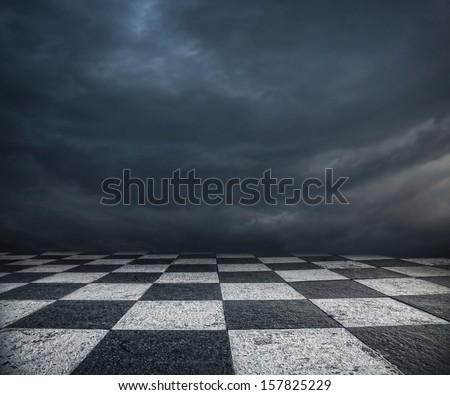 Chess floor and dramatic overcast sky premade background - stock photo