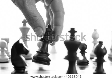Chess game black queen advances b&w close up of hand - stock photo