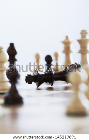Chess game king lying on board surrounded by pieces