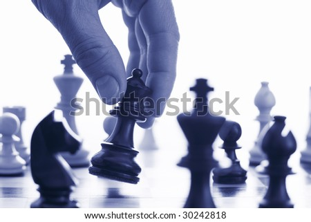 Chess game make your move blue tone close up of hand and chess pieces - stock photo