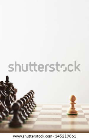 Chess game single white piece in front of black pieces - stock photo