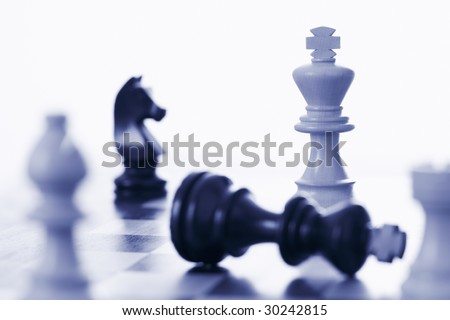 Chess game white king defeating black king blue tone - stock photo
