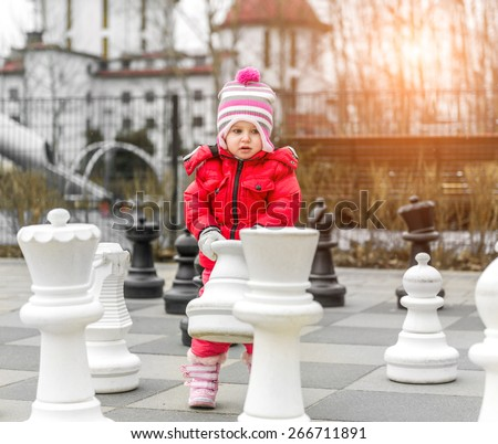 Chess game with giant chess piece. Girl playing strategic outdoor game - stock photo