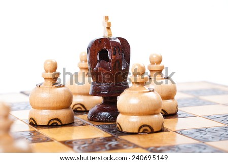Chess Game with lonely black King surrounded by opposing pawns, white background, isolated, space for your text - stock photo