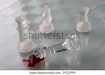 chess game with the opposing king laying in a pool of blood - stock photo