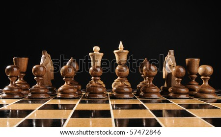 Chess in ranks on black background - stock photo