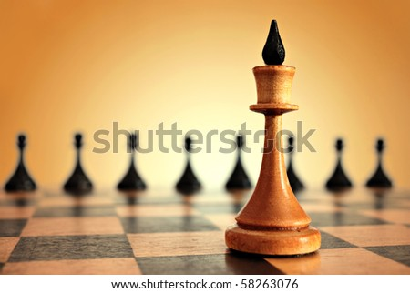 chess king in focus and pawns on blurred background - stock photo