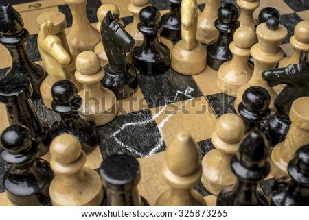 Chess King killed on the chessboard, the witnesses look at the circled using a chalk outline of a corpse - stock photo