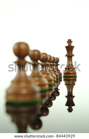 Chess king standing out from his pawns. - stock photo