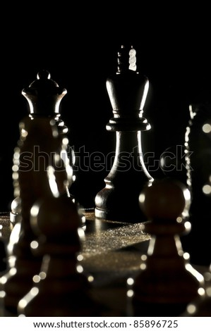 Chess King surrouned by opponent's pawns  lit from the back - stock photo