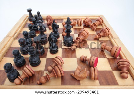 Chess king team leader dominating another in the foreground against a background of black army chips. isolated on white background. - stock photo