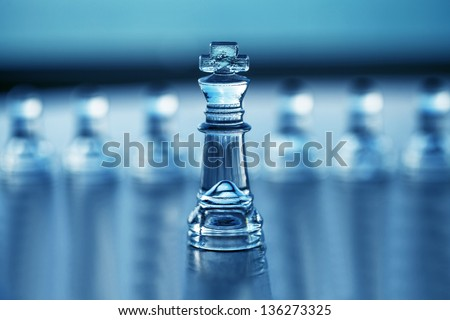 Chess King (with pawns out of focus) - business concept for leadership, strategy, CEO, consulting, mentoring and business advice - authoritative business card design with copy space. - stock photo
