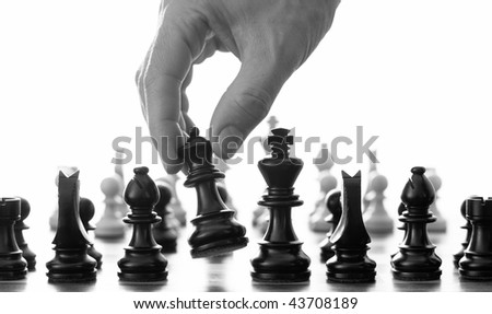 Chess move with hand picking up the queen black and white - stock photo