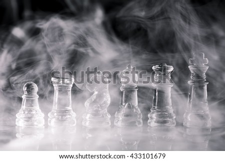 Chess on a black background / Create white smoke and noise assembly./ Glass chess on a black background. - stock photo