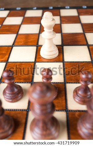 Chess one white king against black figures success business concept.