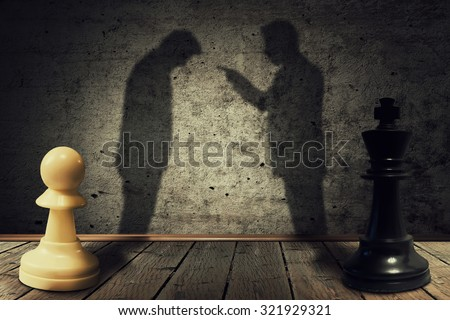 Chess pawn and king standing in front one another with their shadow transform into businessman silhouettes. Business hierarchy misunderstanding - stock photo