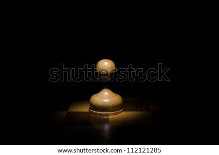 Chess piece pawn against a  black background close up - stock photo