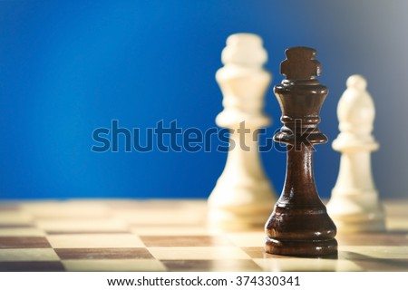 Chess pieces and game board on blue background - stock photo