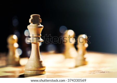 Chess pieces and game board on dark background - stock photo