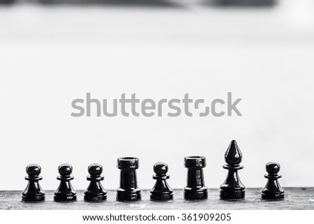 Chess pieces in a row on the wood plank in winter day. Closeup picture.