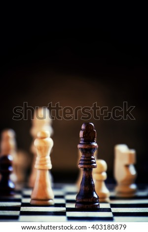 Chess pieces on a chessboard, black background, selective focus, shallow depth of field - stock photo