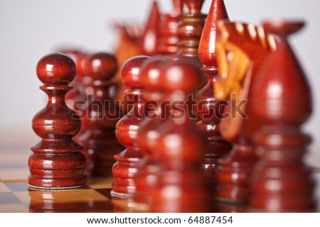 Chess pieces on board (focus on center pawn) - stock photo