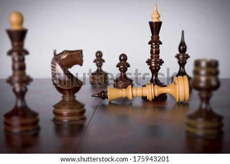 Chess pieces on chessboard. Checkmate to white king - stock photo